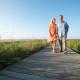 Couple walking on boardwalk through grass