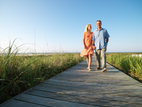 Couple walking on boardwalk through grass