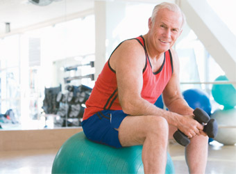 Senior man with weights at gym