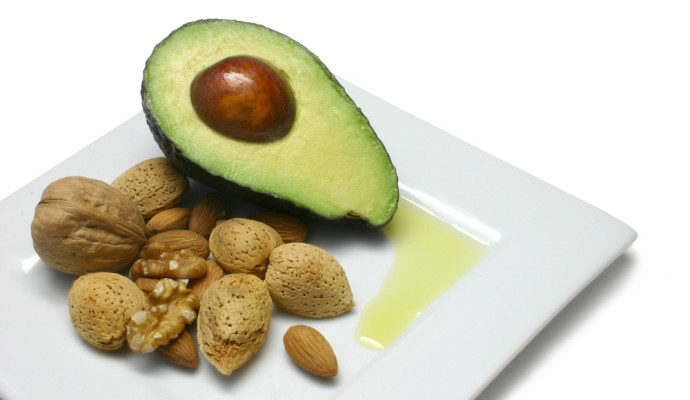 Avocado, nuts and olive oil on plate