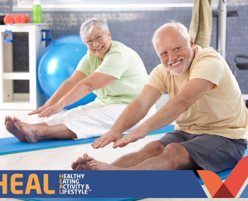 Older man and woman stretching in gym