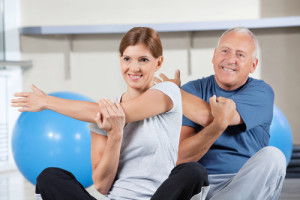 Man and woman stretching in gym