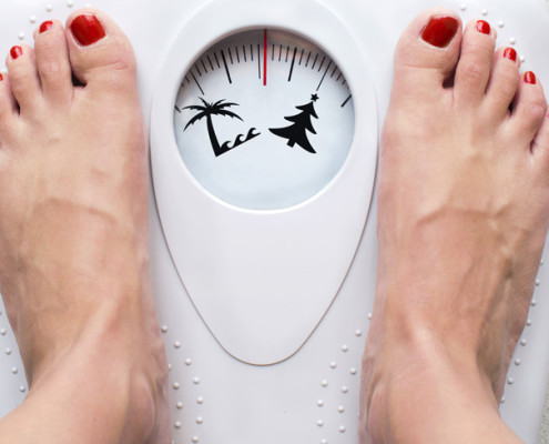 Women's feet on scales with palm tree and Christmas tree