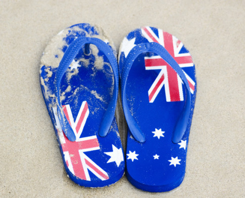 Thongs with Australian flag pattern on sand at beach