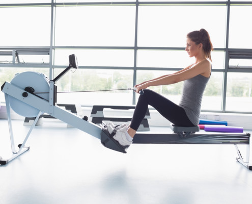 Woman on rowing machine in front of window