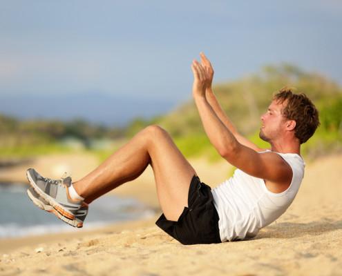Man doing crunches on beach
