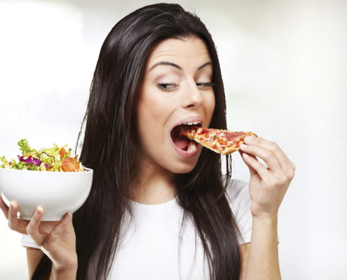 Woman eating pizza instead of salad