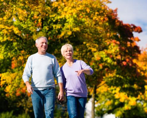 Older couple walking through park