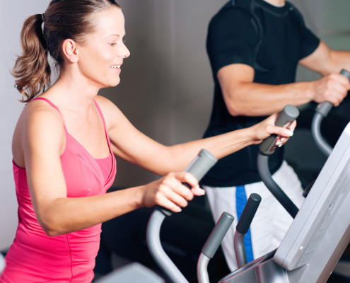 Woman and man training side by side on exercise equipment