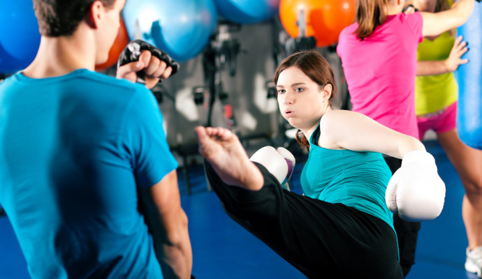 Woman kick-boxing in gym with male partner