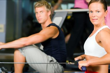 Man and woman rowing in gym