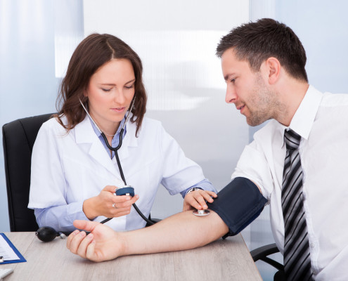 Nurse taking mans blood pressure